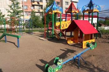 Детская площадка с красным игрушечным домиком