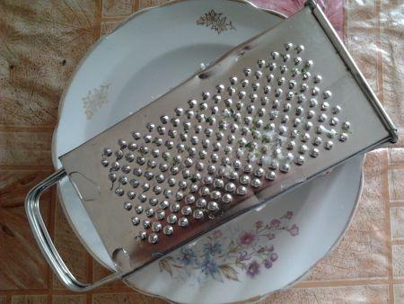 Грязная терка на тарелке с водой